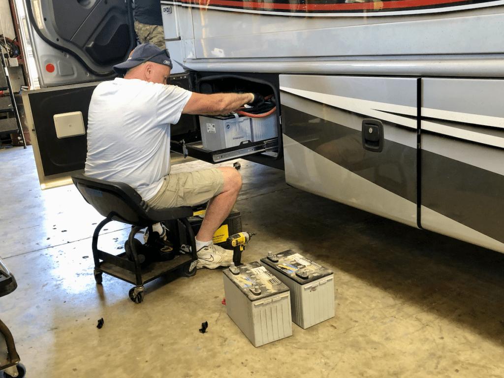 RV mechanic replacing batteries in a motorhome